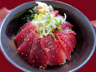 Black bowl full of sliced sashimi tuna on rice