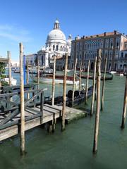 Boats and gondolas along a canal in Venice, Italy with Basilica di Santa Maria della Salute