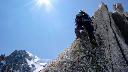 a rock climber on an exposed granite ridge in the French Alps near Chamonix with Mont Blanc in the background