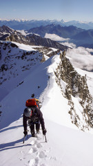 a mountain climber on the summit ridge after a climb through a steep north face in the Italian Alps