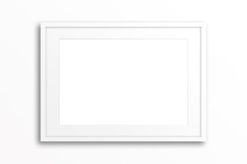 Blank white frame on plain wall. Interior decor mock up
