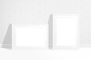 Blank photo frames near white bricks wall
