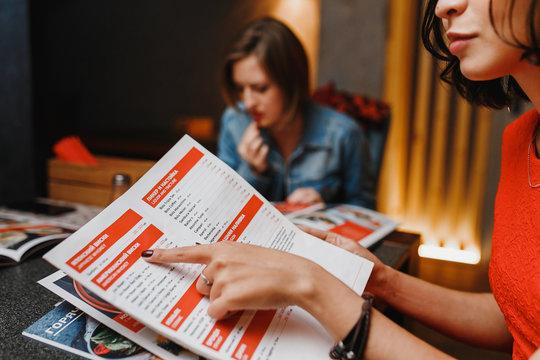 girlfriends in cafe night club choose the food menu