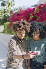 Smiling female friends using smartphone outdoors