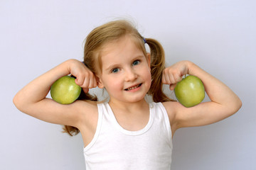 little girl with green apples showing biceps.