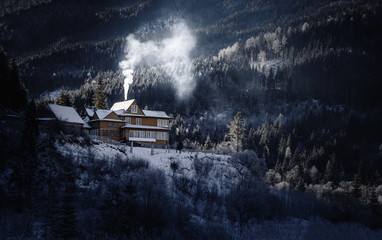 House in mountains. Winter scene. Lonely life in wild nature concept.