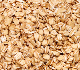 Background of golden oat flakes. Healthy food. Close up, top view, high resolution product.