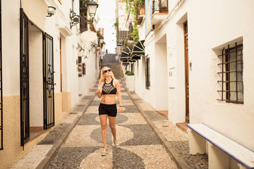 Female tourist looking up whilst strolling along street, Altea, Alicante Province, Spain