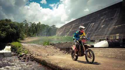 off road dirt bike rider by dam in hard enduro rallying race