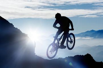 springender Mountainbiker im Gebirge im Gegenlicht