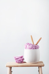 Balls of cotton yarn in pink with crocheted afghan squares