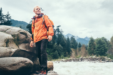 Man Traveler with backpack on the mountain river bank