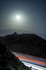 Large full moon or supermoon over a long exposure of a highway or freeway.  The travelling cars are blurred from motion.