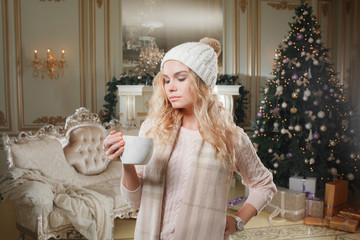 Christmas evening. Young beautiful blonde woman with cup of coffee in classic apartments a white fireplace, decorated tree.