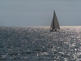 small sailboat sailing in a sparkling sea