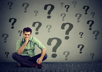 business man sitting on a floor with many questions what to do next