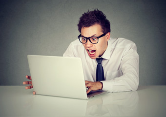 Angry business man screaming at computer