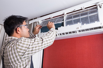 Young man electrician cleaning air conditioning in client house