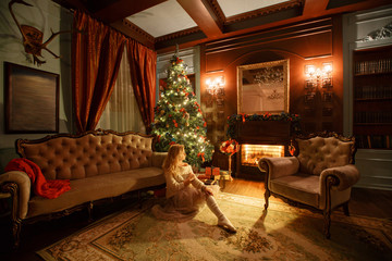 Christmas evening. Young beautiful blonde woman in classic apartments a white fireplace, decorated tree.
