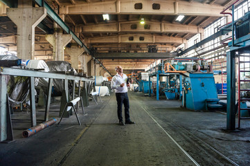 Mature man standing in factory