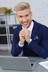 lächelnder mann sitzt am schreibtisch im büro