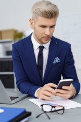 geschäftsmann sitzt am schreibtisch und schaut auf sein handy