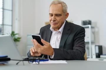 unternehmer im büro schaut zufrieden auf sein mobiltelefon