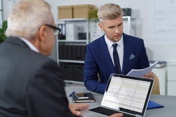 zwei männer im büro arbeiten zusammen und schauen auf unterlagen