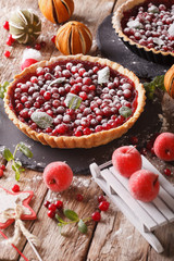 Delicious Christmas cranberry tart and festive decoration close-up. vertical