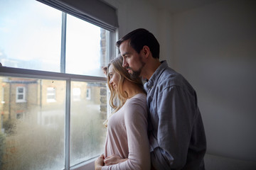 Young couple looking through window