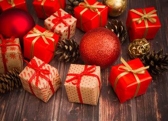 Christmas or New Year background: gifts, colored glass balls, decoration and cones on wooden background