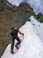 a mountain climber on a steep mountain face in the Swiss Alps near Zermatt