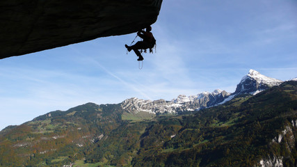 a mountain climber aid climbing a gigantic roof in the Swiss Alps
