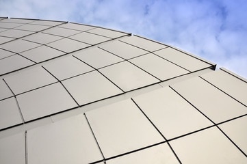 Detail of a circular facade of a modern building made of sandwich panels on a blue sky background.