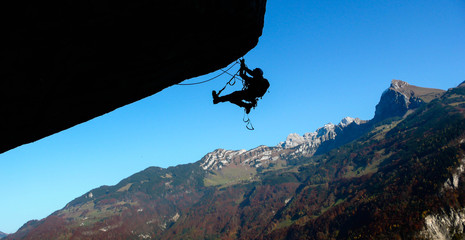 a mountain climber on a technical climb of a giant roof in the Swiss Alps