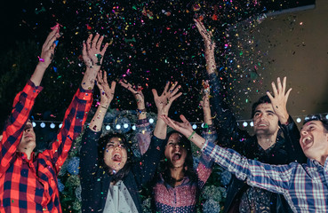 Close up of happy young friends raising their arms and having fun among the colorful confetti in a outdoors party
