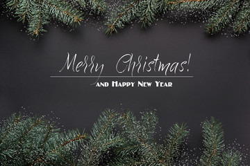 Christmas or New Year decoration background. Fir tree branches on black background. Top view. Holiday card. Drawn snow.