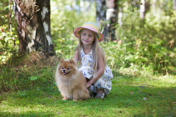 Girl walks with her beloved dog in the woods in a sunny summer day. Girl in hat hugging her Spitz.