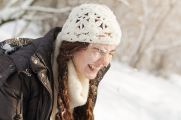 Long-haired brunette girl walking in a winter park and playing with snow, wearing  white sweater and a handmade white hat