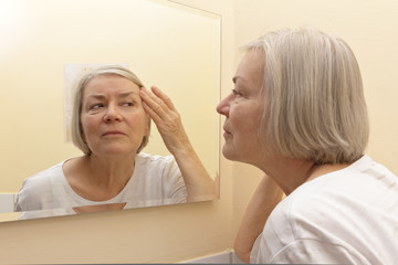 woman examining face skin mirror