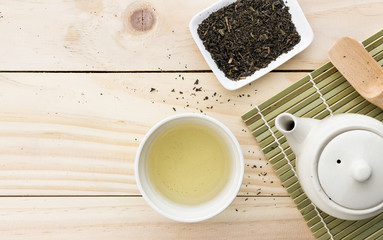 cup with green tea and teapot on wooden table background. over light