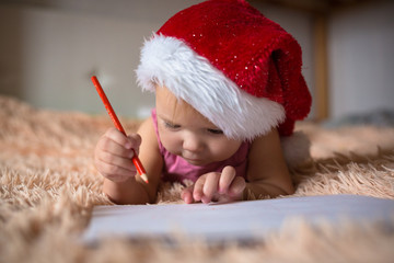 Child Toddler in  Christmas cap writing  letter to Santa Claus,