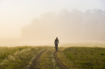 Girl ride on bicycle in autumn misty morning. Original sport wallaper