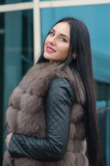 Beautiful girl with a smile in fur waistcoat