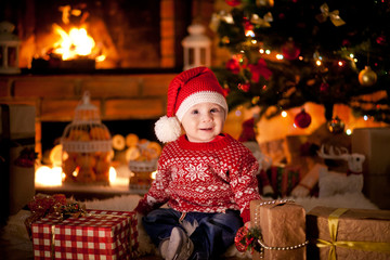 A little boy dressed as Santa in a Christmas interior with a Christmas tree, fireplace and gifts