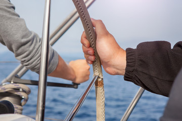 man hand holding a sailing vessel wheel.the sea in the background