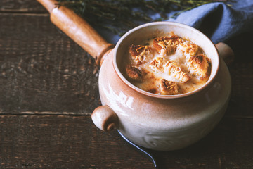 Ceramic pot with onion soup on the wooden table  horizontal