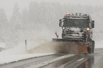Schneepflug auf verschneiter Strasse