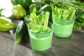 Glasses of fresh vegetable smoothie on wooden table