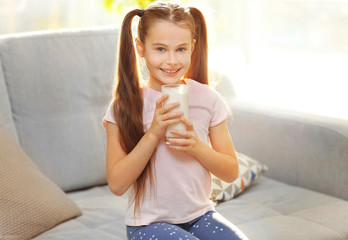 Cute little girl with glass of fresh milk on couch